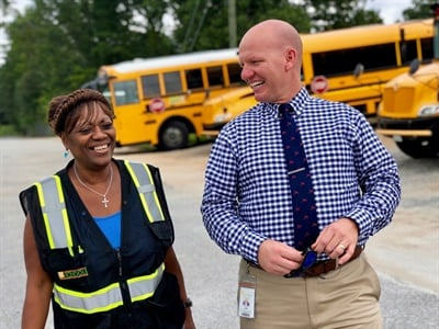 As a pupil transportation director, Adam James applies leadership principles he learned in the Marines, such as knowing his team and looking out for their welfare. He is seen here with bus aide Belinda Williams.