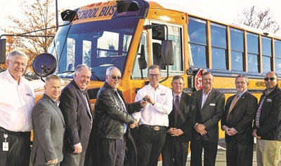 Ken Hedgecock (shown left) helped introduce the Saf-T-Liner C2 in 2004. Caley Edgerly, president and CEO of Thomas Built Buses (shown center), hands the keys for the first Saf-T-Liner C2 equipped with the new Detroit DD5 engine to Henrico County (Va.) Public Schools in 2018. Photo courtesy Thomas Built Buses