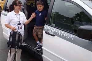 American Logistics Co. arranges alternative transportation services for school districts. Here, a driver helps a student out of a van.
