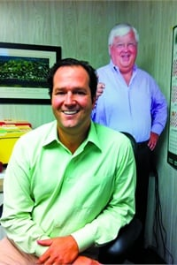 Gray Ellison is CEO of SMI, which supplies a variety of safety and interior products for school buses, including stop arms, crossing arms and roof hatches. In the background is a cutout of industry veteran Buck Pearce, who retired from SMI in 2007.