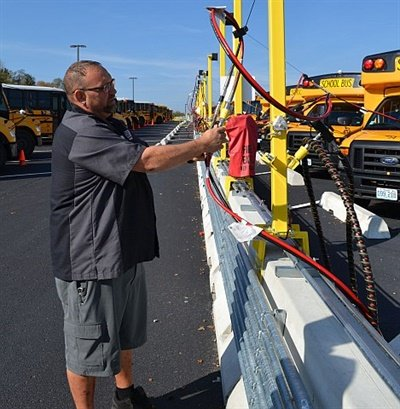 In August, Blue Springs School District launched a new CNG fueling station that will eventually feed 120 CNG buses. Seen here is Jason Cain, lead mechanic for the district. Photo courtesy Collins Bus Corp.