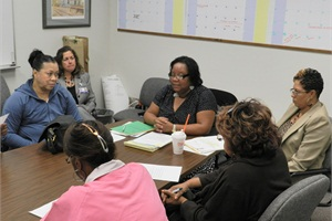 Rike and two of her transportation supervisors, Michelle Beasley (center) and Veronica Norfleet (far right), hold a meeting with a group of new drivers.