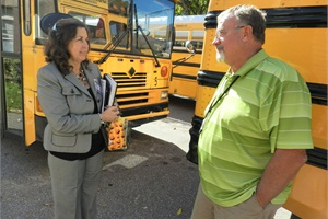 Debbie Rike, director of transportation for Shelby County Schools, talks with bus driver Curby White outside of Shadowlawn Middle School.