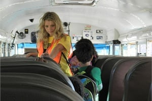 Third-grade teacher Brianna Gould keeps bus passengers on their best behavior as part of the Rough Riders program.