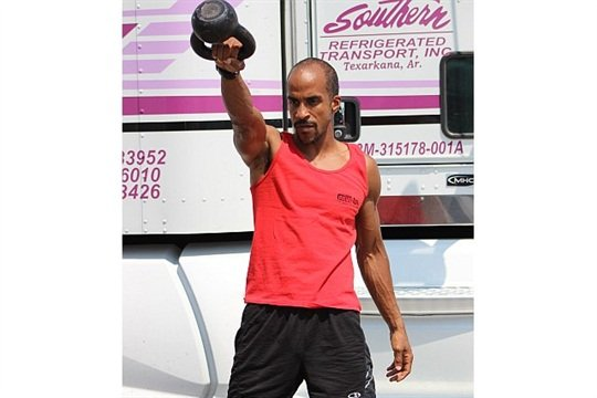 "Baleka says that drivers can do his workouts ""on the side of their truck or on the side of a school bus — or pretty much anywhere."" Here, he does single-arm swings with a 20-pound kettlebell."