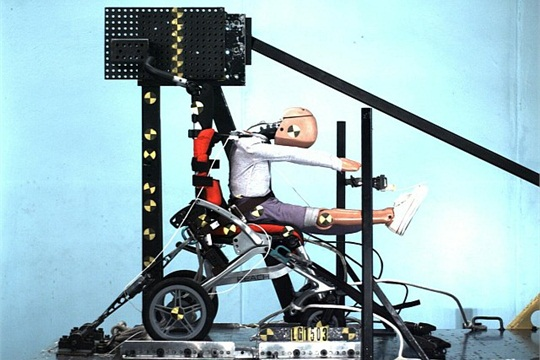 This peak-of-action photo from high-speed side view video shows a Reach pediatric wheelchair protecting a 6-year-old crash-test dummy in a 30 mph frontal sled-impact test by a five-point wheelchair-integrated harness. Photo courtesy of UMTRI with permission from Leggero LLC