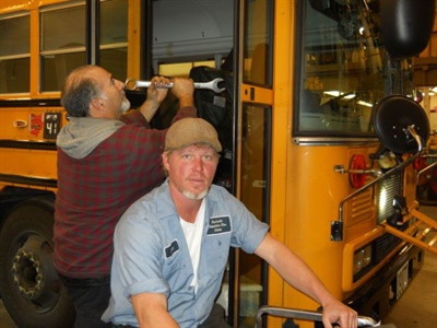 Maintenance staff members, including Bart Hahn (right), follow a three-part inspection schedule for every bus.