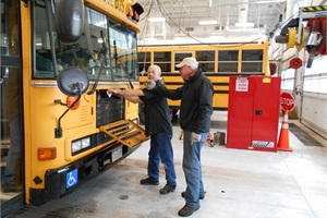 At Adams 12 Five Star Schools in Thornton, Colo., the transportation facility features a drive-through lane so that drivers/buses can pull in the shop and get what repairs they need while they wait, and also discuss concerns with the technicians. Pictured are technician Don Hough (left) and driver Les Shannon.