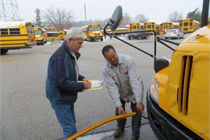 "Parkway School District bus driver Chuck Deem (left) and technician Ben Thompson inspect a crossing arm. Will Rosa, director of transportation for the Missouri district, says that drivers and technicians at his operation have been successful at not buying into the notion that each group doesn't do their job thoroughly or correctly, and they ""channel their energy toward the problem, not the person."""