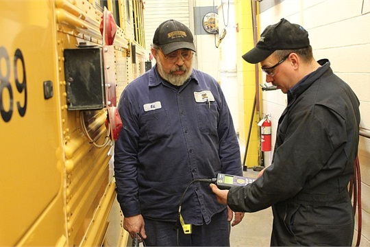 Shenendehowa technicians Eddie Hernandez (left) and Mike Peek use a battery scanner on one of the district's buses.