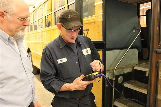 George Geel (left), Shenendehowa Central School District's fleet maintenance supervisor, and technician Wesley Montgomery run diagnostics on a bus with a PocketMaxx scan tool.