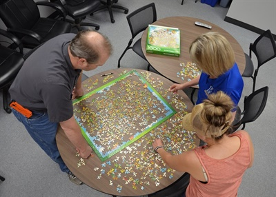 Becky Reier, director of transportation for Kearney (Neb.) Public Schools, (pictured top right), uses jigsaw puzzles to foster a sense of community among her staff members. Photo courtesy Rick Brown