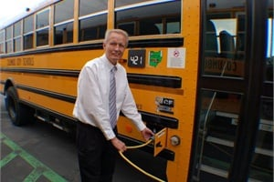 Phil Downs, manager of fleet services for Columbus City Schools, is pictured plugging in one of the district's IC Bus hybrid school buses.