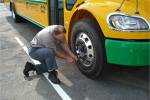 As part of his daily routine, Equipment Service Technician Mike Smith checks the tire pressure on a C2e.