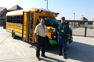 Flores (left) is pictured with the district's former director of transportation, John Clements. Clements was instrumental in getting grants for the district to obtain four Trans Tech Bus SSTe school buses.