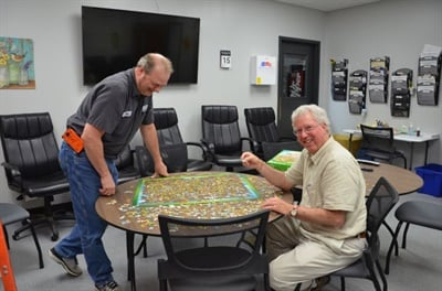 Kearney Public Schools mechanic John Baughman (left) and driver Rick Brown work on a jigsaw puzzle in the transportation staff lounge.