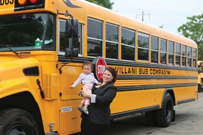Family-run Villani Bus Co. has grown by leaps and bounds over the last century, now transporting over 7,500 students every day. Shown here is Courtney Villani, president, with her son, Diodato.
