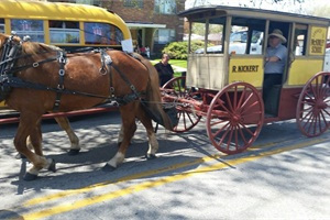 "Kickert's first ""school bus"" was a horse-drawn wagon fitted with board seats, as seen here in a parade in May."