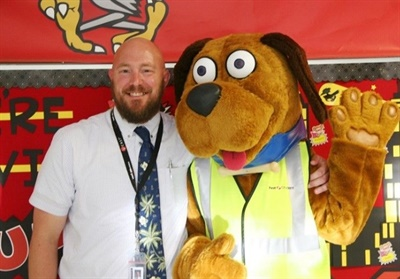 Andy Place, one of the school district's principals, is a member of the PBIS Transportation Committee. He is shown here with Safety Dog, First Student's mascot.