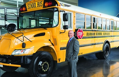 National Express LLC's operations, including Durham School Services, transport more than 1 million students daily with 21,500 school buses. CEO David A. Duke is seen here with a new IC Bus model.