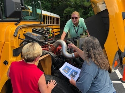 Jackson County trainers (from left) Tina Johnson, Kim Nash, and Anita Sears inspect an engine, which is part of state-required driver training.