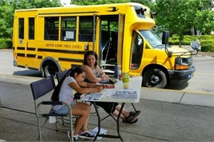 Greater Albany Public Schools transportation staff talk to parents at events as Oregon schools start switching from half-day to full-day kindergarten. Shown here are a student and a driver trainer at an event held over the summer that let students and parents see the school bus.