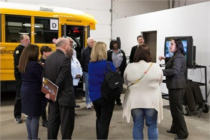 New York School Bus Contractors Association members, Suffolk Transportation employees and the Suffolk Region PTA showed parents and district officials bus safety features and safety training requirements for school bus drivers. Shown far right is Hilma Hammer, regional director at Suffolk Transportation, discussing evacuation procedures.
