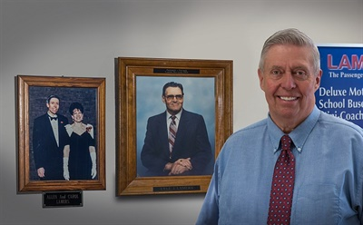 In 1944, founders Lyle (shown in the portrait to the right) and Ellen Lamers founded the bus company, and their growing family hasn't stopped building the business since. Pictured here is Allen Lamers, the company's president, posing next to some family photos in the company's headquarters in Green Bay.