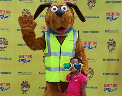 "A student poses with First Student's ""Safety Dog"" as part of the company's safety event in Woodland Hills, Pennsylvania, in 2016."