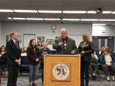 Greg Hoeger (pictured center), a driver for Carson City (Nev.) School District, was honored at a school board meeting on Dec. 11 for saving the life of a student passenger. Photo courtesy Carson City School District