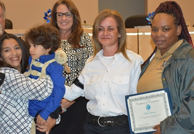 Volusia County (Fla.) Schools special-needs bus driver Sonia Rivera (pictured second from right) and bus aide Tiffany Bryant (right) were recognized at a Deltona City Commission meeting for helping save Lily Gonzalez (left) and her special-needs son from a speeding car. Photo courtesy Deltona City Commission