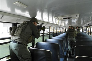 SWAT team members sweep a school bus after the live-action event that simulated a response to an active shooter.