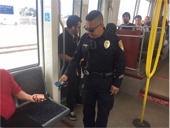Code Compliance Inspector, Ricardo Favela, checks a passenger's transit fare during a routine inspection onboard an MTS Trolley.  