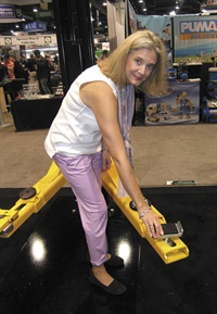 Kristen Simpson shows a new truck frame adapter for Rotary LIft's Trio Arms system.