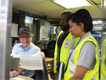 System Safety representatives Jason Connor and Carrie Givhan discussing SEPTA's safety survey results with Market-Frankford Line cashier Frank Gailey. Photo: SEPTA