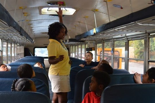 A Marietta school bus driver on the SOAR team shows students a roof hatch, one of the emergency exits on the bus.