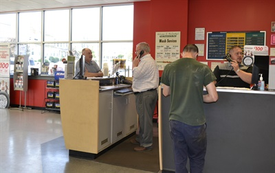 "At 2019 Tire Dealer of the Year John McCarthy Jr.'s stores, the retail counter serves as ""the front door"" for the dealership, says McCarthy. Here Guy Westerholm, left, and Jordan Davis work with customers in the Wilkes-Barre, Pa., store."