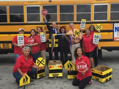 """At a district-wide convocation, the transportation team wore school bus costumes, waved signs, and won the district's """"spirit stick"""" award."""