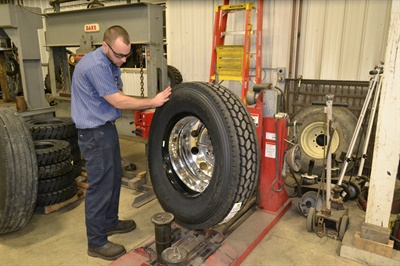 Commercial tire sales and service make up more than half of Schnipke Brothers Tire's total revenue. Here, Andrew Schnipke mounts a Roadmaster truck tire.