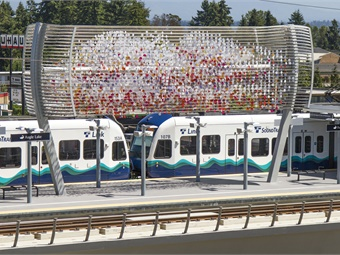 "Artist Laura Haddad's ""Cloud"" sculpture, made of 6,000 eco-resin disks that glimmer with variations in sunlight and wind, hangs above the train platform as a prominent visual element of the station.