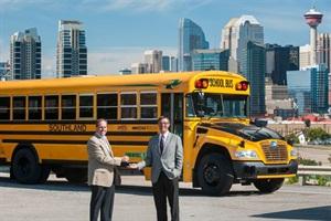 Jason Kirkman (left) of Kirkman Bus Sales hands Blue Bird Propane Vision keys to Tom Jezersek of Southland Transportation.