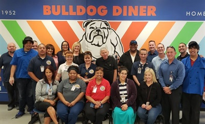 The Clark County transportation department's breakfast meetings take place at the Bulldog Café, operated by special-education students. Each month, Executive Director Shannon Evans (back row, next to bulldog) connects with a small group of drivers and other staff members.