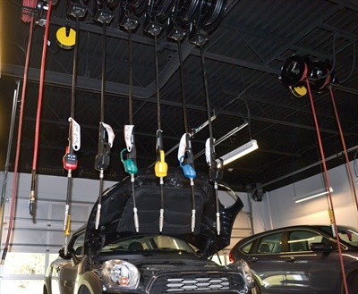 Six different viscosities of motor oil hang at the ready, with the washer fluid hose next to them.