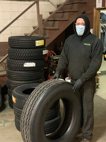 Sullivan Tire's Chrystian Soto dons a mask and gloves while handling tires.