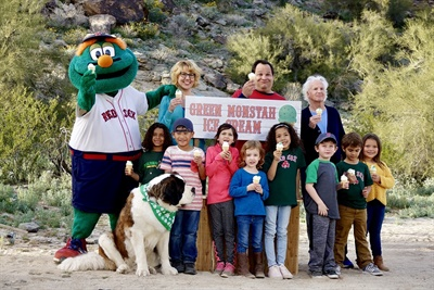 Boston Red Sox mascot Wally the Green Monster stars in Sullivan Tire's latest television commercials. Pictured are (back row, left to right):  Wally, April Walterscheid, Javier Gilmore, Paul Sullivan, (front row, left to right): Tally the dog, Jaxson Wells, Carter Quan, Claire Boatman, Azra Kearns, Leah Jones, Dane Goldapper, Adam Jackson and Jacquelyn Fuchs.