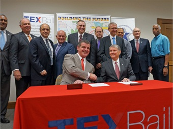 Following the contract signing ceremony for TEX Rail vehicles, Paul Ballard, president and CEO of the Fort Worth Transportation Authority (The T) (seated right) and Stadler President/and Chairman Peter Spuhler (seated left) pose with The T's board members, including T Board Chair Scott Mahaffey (standing 2nd from left), other Stadler officials and Fort Worth area transit advocates.