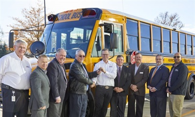 Caley Edgerly, president and CEO of Thomas Built Buses (center), hands over the keys for the first Saf-T-Liner C2 school bus equipped with the Detroit DD5 engine to Josh Davis, the director of pupil transportation for Henrico County (Va.) Public Schools (fourth from the left.)