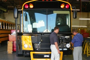 Thomas Built Buses engineers review an array of recently installed upgrades on a prototype of the EFX.