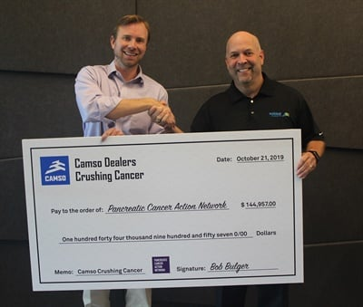 Tim Varner (left) of the Pancreatic Cancer Action Network accepts the donation raised by the Camso Crushing Cancer program from Bob Bulger, vice president and general manager-North America for Camso.