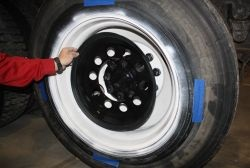 The Minimizer Tire Mask kit comes with a tire mask (held in place by the blue tape in the picture) that protects tires from paint and primer overspray.